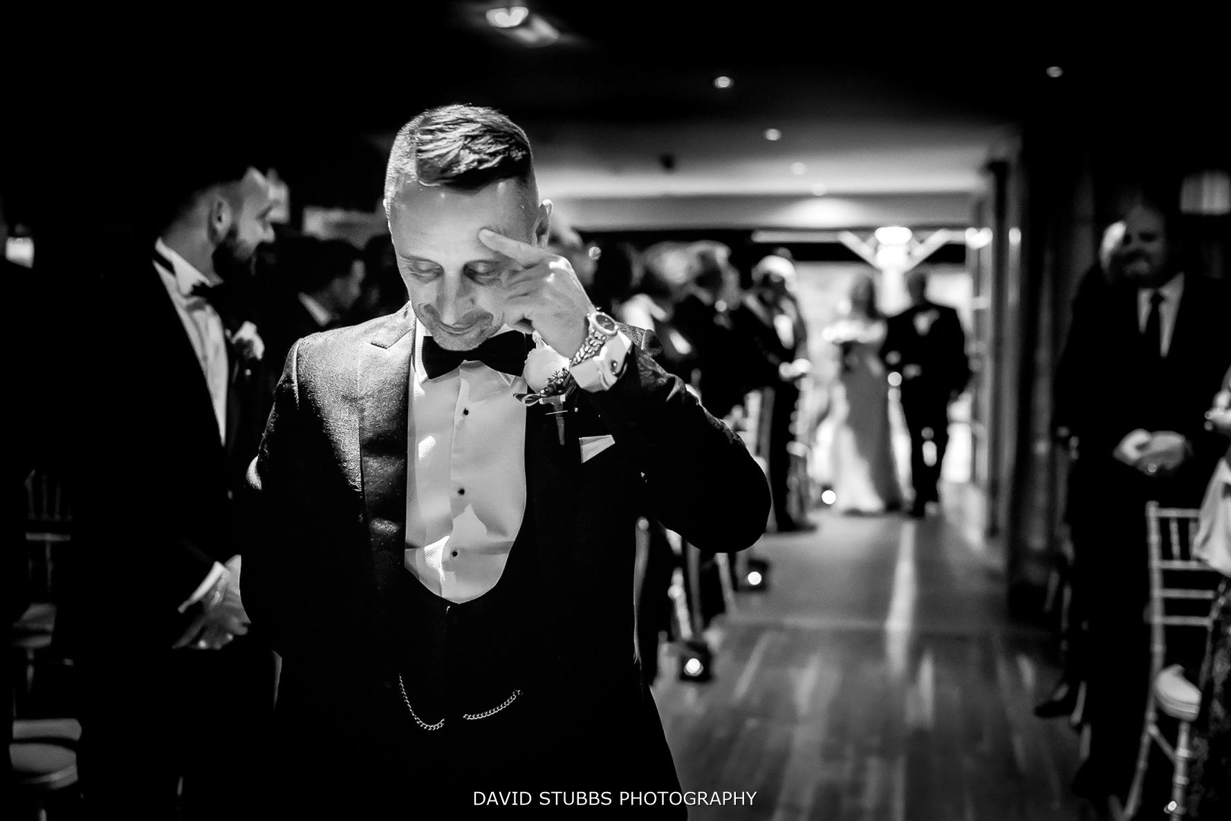 tear in the grooms eyes as bride walks down the isle