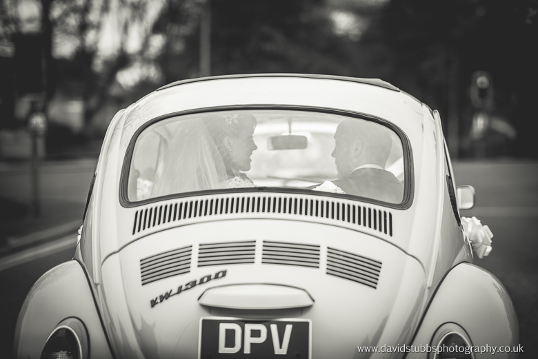 bride and groom inside vw beetle on their way to stirk house wedding