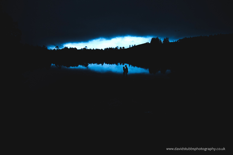 couple in distance against water and clouds