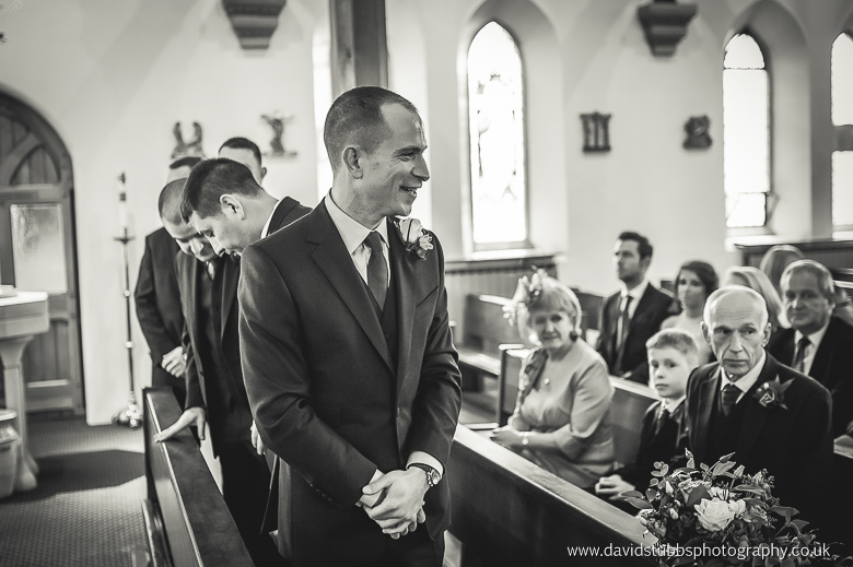 groom waiting at top of aisle