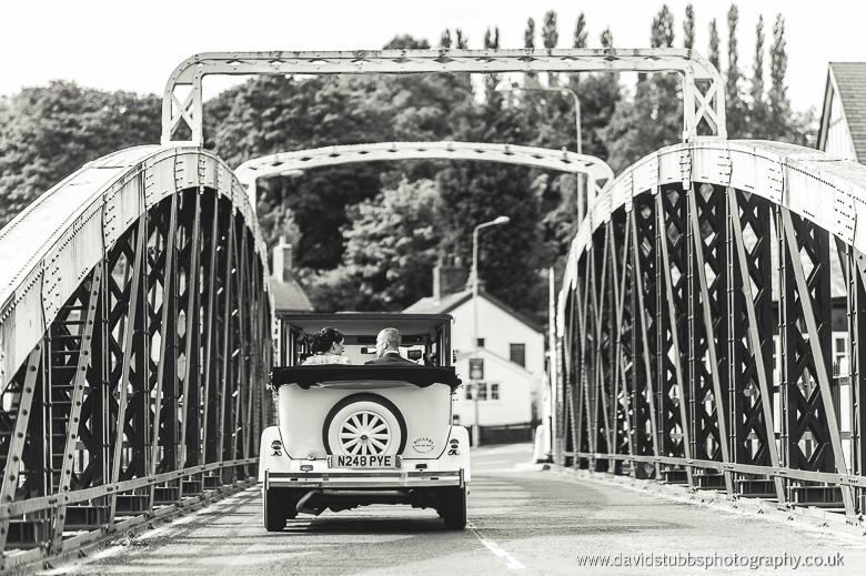 wedding car driving away over bridge