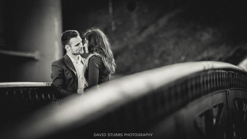 black and white photo of engaged couple on bridge