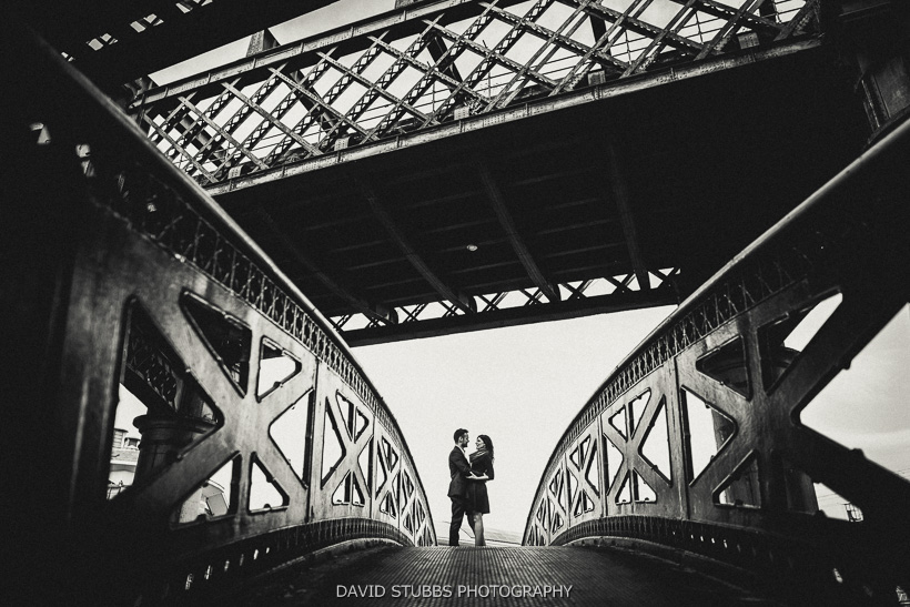 black and white photo of couple on bridge