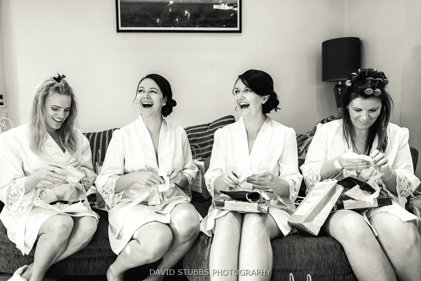 bridesmaids laughing on couch black and white