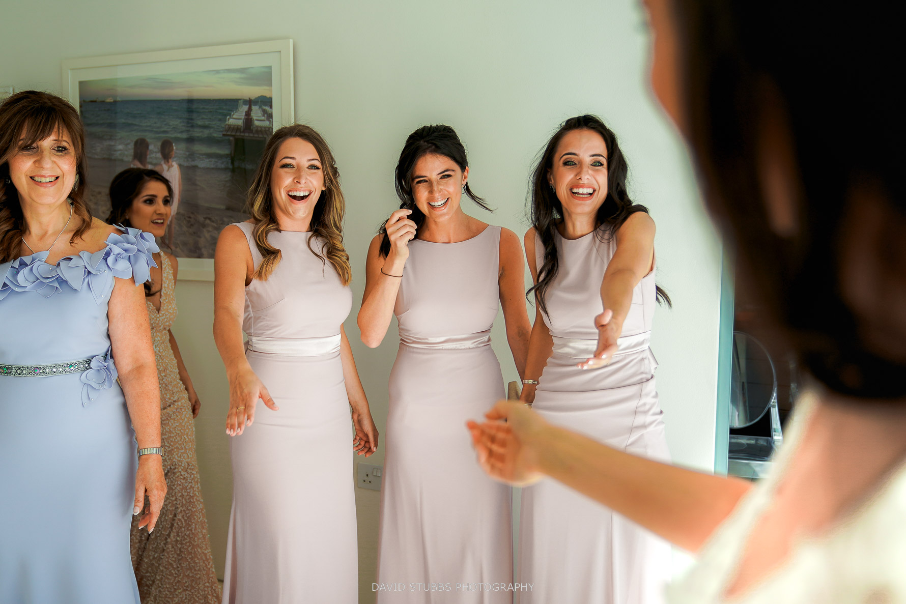 bridesmaids seeing the bride fo the first time in her wedding dress
