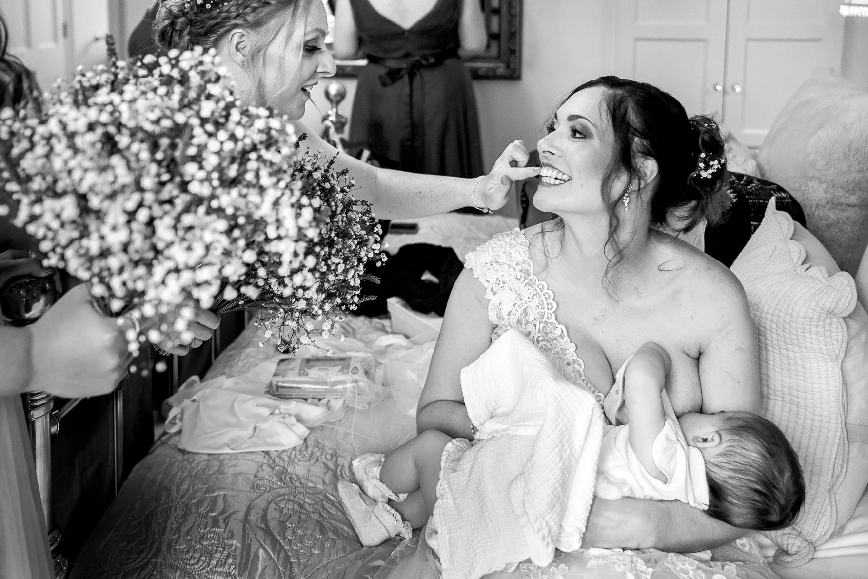 bride breastfeding her baby at her wedding