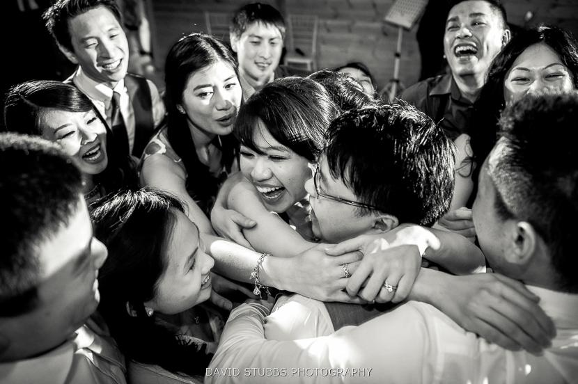friends hugging bride and groom