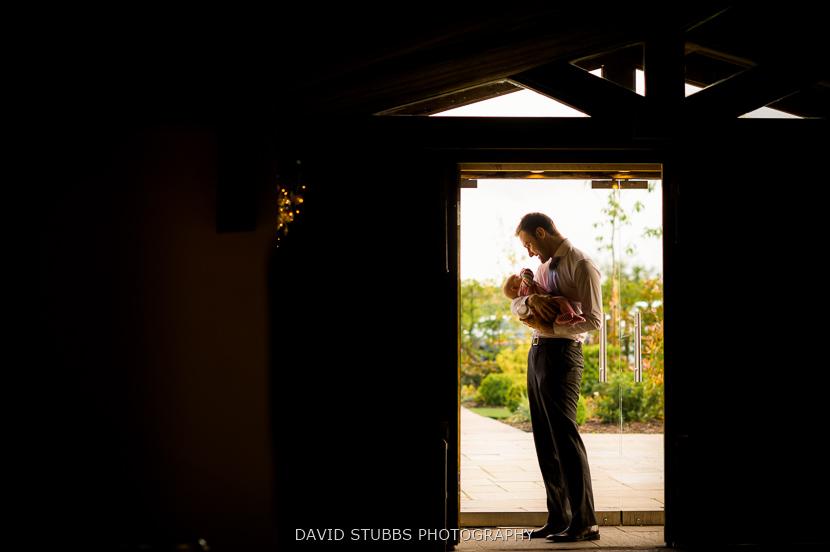 man with baby in doorway