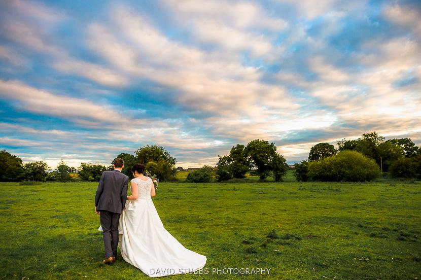 married couple walking in field