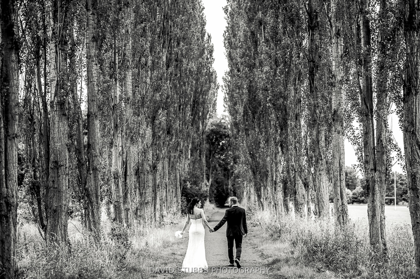 newly-weds walking through trees