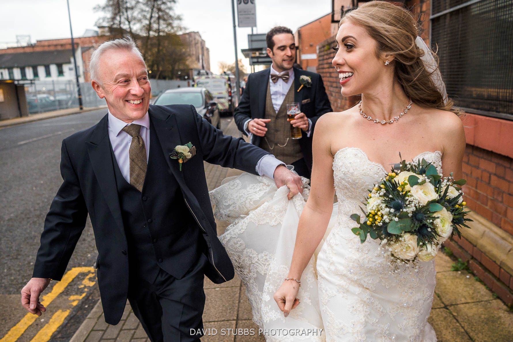 bride and dad carrying wedding dress
