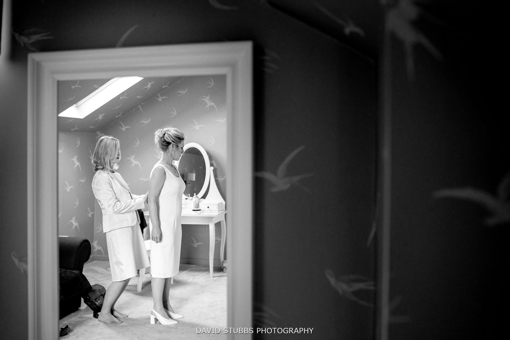 the two brides getting in their wedding dresses