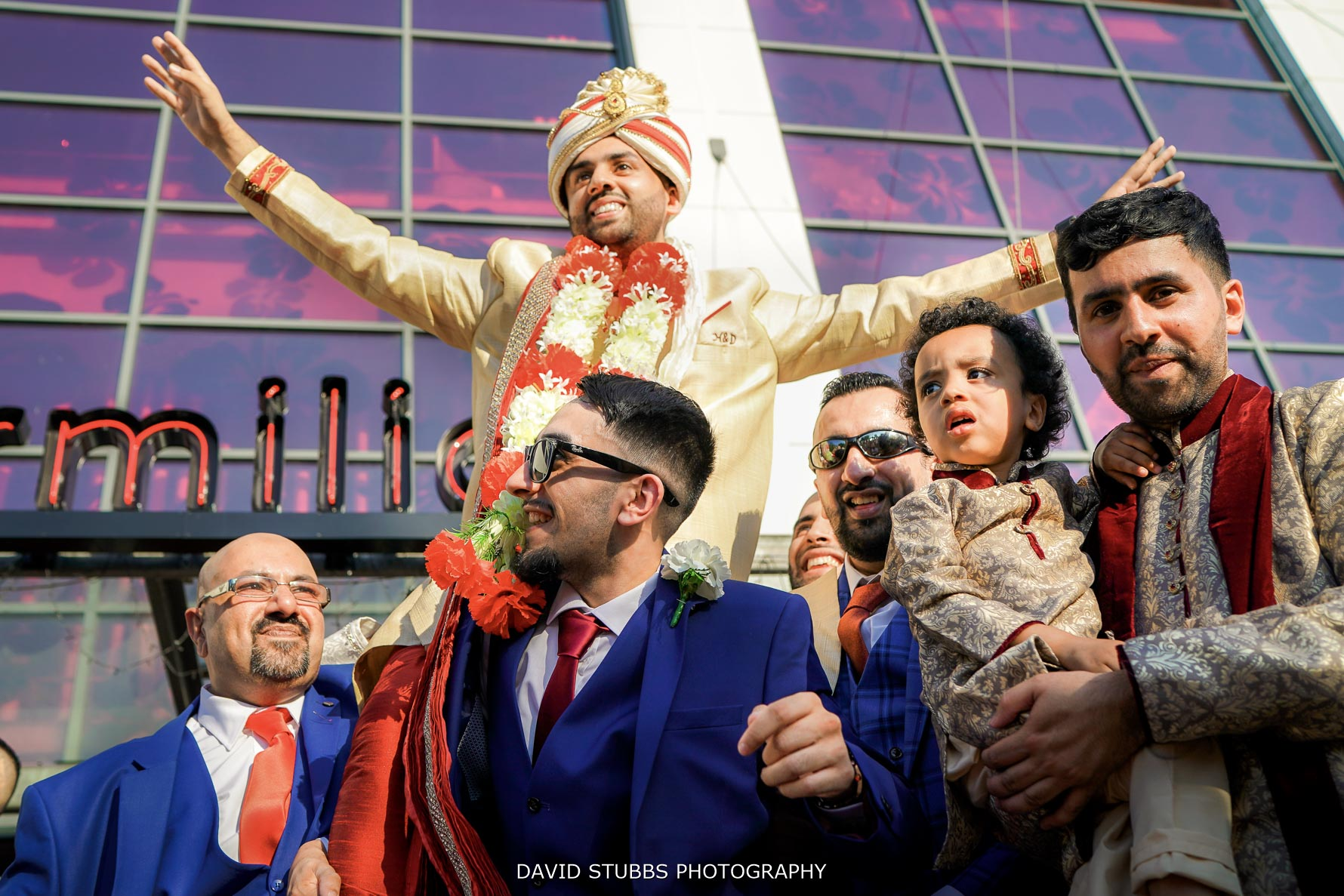 low angle of groom being held above all the groomsmen